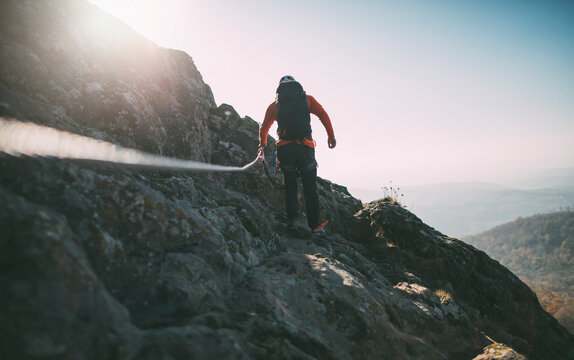 Rear view of man with backpack climbing a mountain using rope