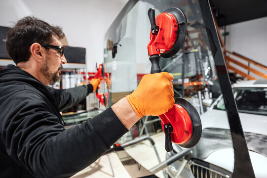 Automobile technician worker replacing windscreen or windshield of a car in auto service station garage. High quality photo