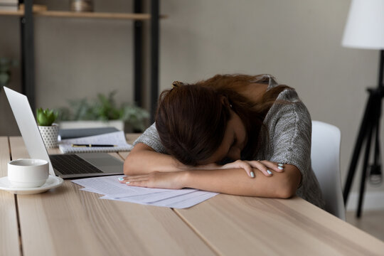 Exhausted unmotivated young female worker fallen asleep at table working with paper documents, feeling lack of energy at workplace, sleepy woman tired of exam preparing or studying at home office.