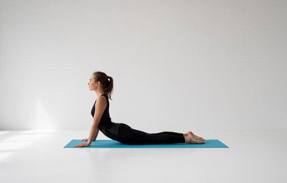 Young woman practicing yoga, lying and stretching in Cobra pose, doing Bhujangasana exercise. Attractive girl in black sportswear. Beautiful sporty fit yogini woman practices yoga asana bhujangasana.