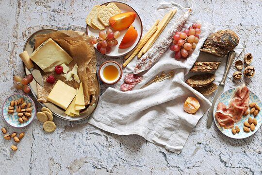 Appetizers table with various of cheese, curred meat, sausage, olives, nuts and fruits. Festive family or party snack concept. Overhead view.