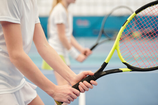Hands of active teenage girl standing on stadium and holding tennis racket
