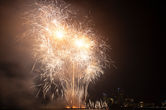 Firework festival with beach foreground and city background at Pattaya beach, Thailand. Colorful firework in celebration festival background