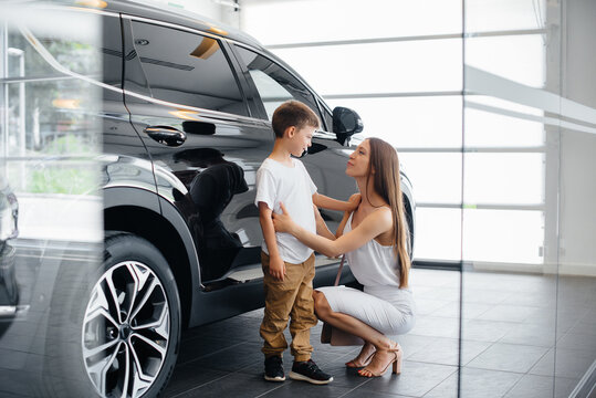 A happy mother with her young son chooses a new car at a car dealership. Buying a car