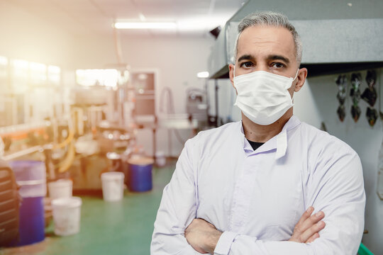 Confidence european high skilled worker middle age 40-50 standing portrait in factory with face mask.