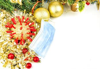 Golden coronavirus, mask and Christmas baubles isolated on white background
