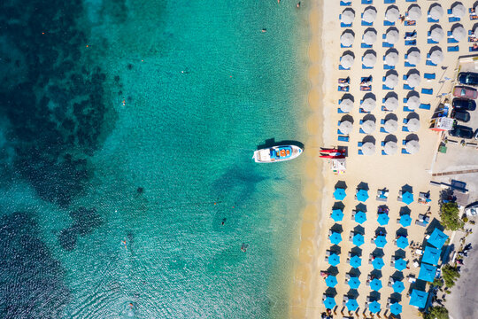 Aerial top down view to the umbrellas and the turquoise sea at the popular beach of Ornos, Mykonos island, Greece
