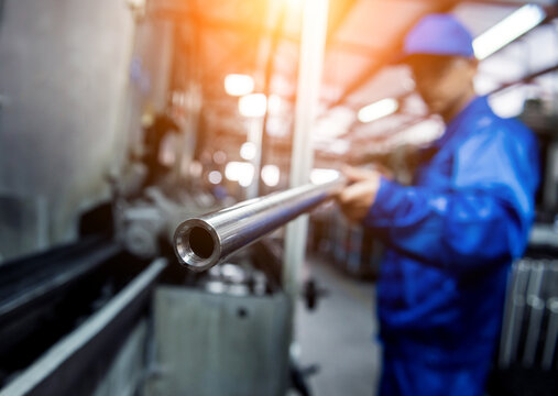 Worker checking metal pipes at a metallurgical plant