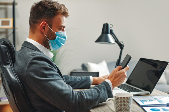 Young man with a virus protection mask working on laptop in the office and use a smartphone