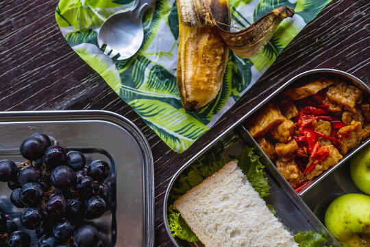 Healthy vegan meal in eco-friendly kitchen tableware: stainless metal food container or lunch box, beeswax wraps with spork on wooden background. Zero waste and sustainable plastic free lifestyle
