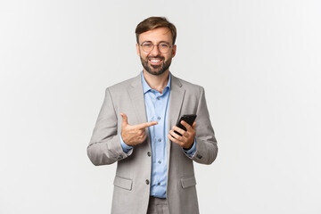Image of handsome male entrepreneur with beard, wearing glasses and gray suit, pointing at mobile...