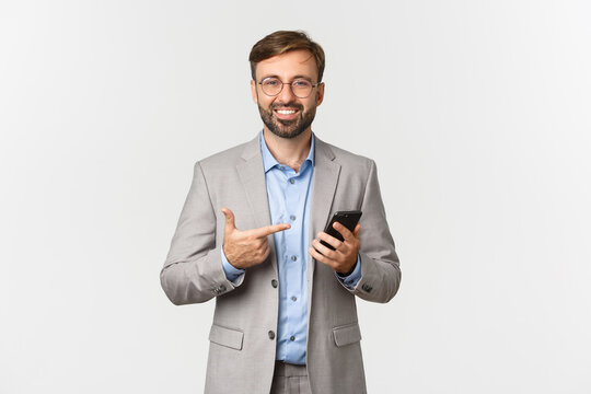 Image of handsome male entrepreneur with beard, wearing glasses and gray suit, pointing at mobile phone with pleased smile, showing application, standing over white background