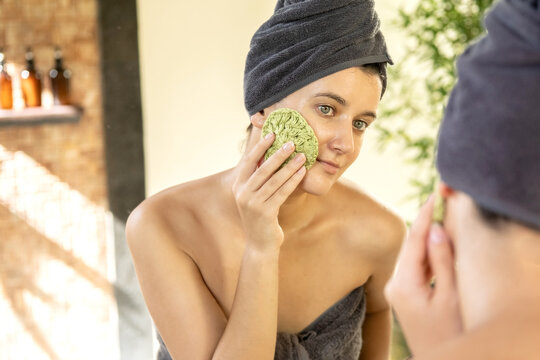 Young woman washing her face with reusable round crocheted pad in bathroom. DIY washable knitted makeup remover cloth. Eco-friendly cosmetic products. Zero waste sustainable plastic free lifestyle