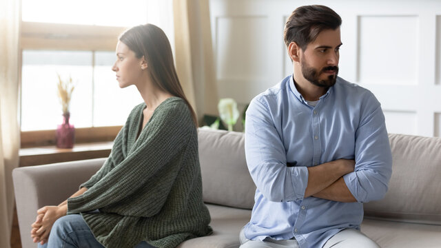 Angry young Caucasian couple sit separate on couch ignore avoid talking after family fight misunderstanding. Unhappy spouses man and woman think of divorce or breakup. Relations problems concept.
