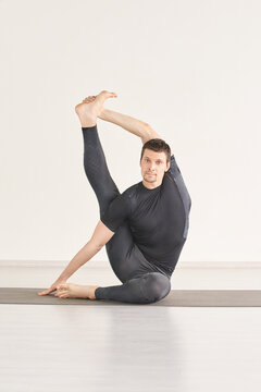 Man in yoga compas asana. Home lockdown studio. One person. Gym fitness. Morning meditating exercise. sport workout. Caucasian male relaxation. Balance energy mudra. Black. Vertical. kraunchasana