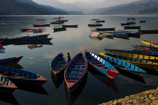 Colorful boats floating with no people anchored on the Phewa Lake, Pokhara, Nepal. Nice reflection of the sky and clouds on the water. Large mountains far away on the background. Post pandemic travel