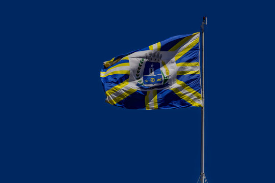 Bandeira da cidade de Anápolis balançando ao vento com o céu azul ao fundo. Foto feita na cidade de Anápolis em Goiás, Brasil.