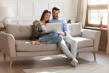 Happy young Caucasian couple renters relax on sofa in living room watch video on laptop together....