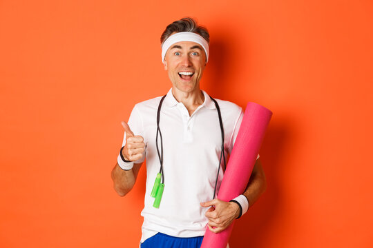 Concept of workout, gym and lifestyle. Cheerful middle-aged fitness guy, holding skipping rope and yoga mat, showing thumbs-up and smiling satisfied, standing over orange background