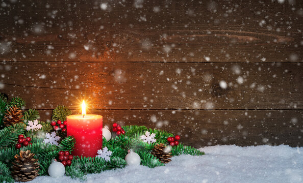 Christmas or Advent wood background with burning red candle on snow and snowflakes, decorated with fir branches and ornaments. Copy Space