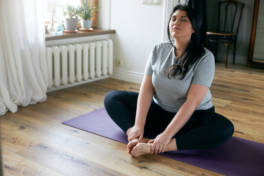 Indoor shot of beautfiful young overweight woman in sportswear sitting on mat doing butterfly yoga exercise, stretching thighs, holding feet and closing eyes, trying to relax body and breath deeply
