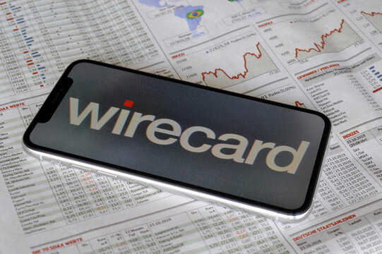 Hamburg, Germany - October 27, 2019: Close-up of a smartphone wih the logo of wirecard AG on a newspaper - Wirecard is a financial services provider headquartered in Aschheim, Germany