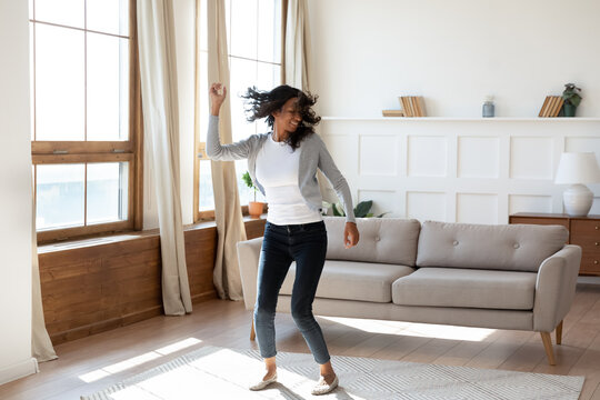 Happy young African American woman tenant relax rest dance alone in cozy light modern living room. Overjoyed smiling millennial biracial female renter have fun enjoy lazy leisure weekend at home.