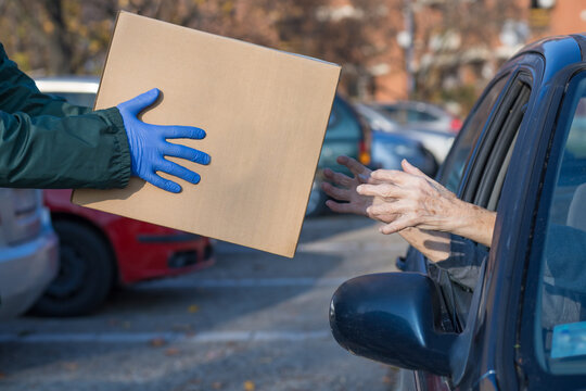 food bank box handed to needy elderly person in vehicle