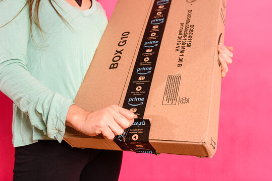 Valencia, Spain - November 28, 2020: Detail of a woman's hand opening an Amazon Prime package during Christmas.