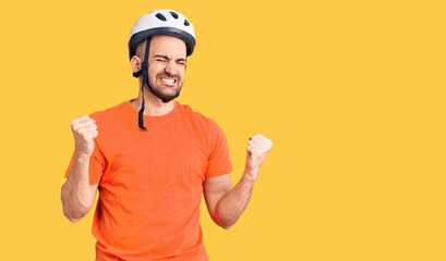 Young handsome man wearing bike helmet very happy and excited doing winner gesture with arms...