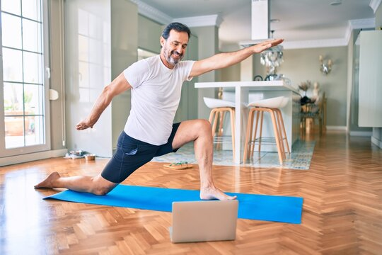 Middle age man with beard training and stretching doing exercise at home looking at yoga video on computer
