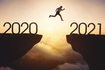 Male entrepreneur jumps a gap from 2020 to 2021 Wall mural
