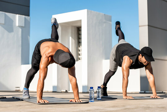 Muscular sports men doing plank leg raise exercise in the open air on building rooftop