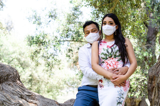 Young loving couple walking in medical masks in the park during quarantine. Coronavirus, disease, protection, sick.