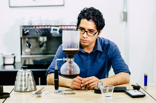 Professional coffee maker - Barista using coffee siphon brewing hot espresso at coffee shop.