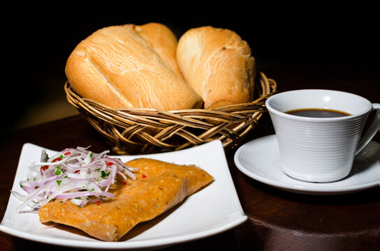 Peruvian breakfast, popular Peruvian tamale with onion sauce, breads and a cup of coffee on a table.