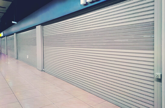 shop exterior with closed shutters. Small business problems during coronavirus pandemic covid19. cafe is closed for quarantine due to covid 19 epidemic. shop window is closed by automatic gates.
