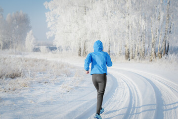 Fototapeta Female runner jogging in cold winter forest.