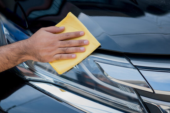The car polisher uses a microfiber cloth and polish to wipe the car's headlamp or headlights to make them shine He takes care of every detail of the car.