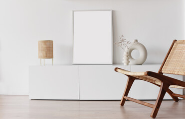 Fototapeta Blank picture frame mockup on white wall. White living room design. View of modern scandinavian style interior with chair. Home staging and minimalism concept