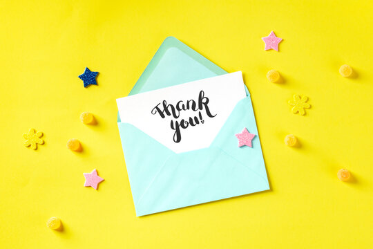 Handwritten Thank You post card in a teal blue envelope, shot from the top on a yellow background with glitter stars and candies