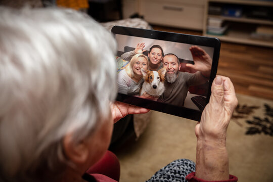 Senior adult is talking via video conference with her family
