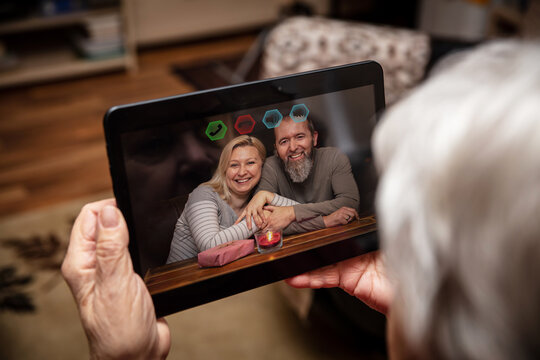 family is video chatting with a female senior adult, holding a tablet in her hands