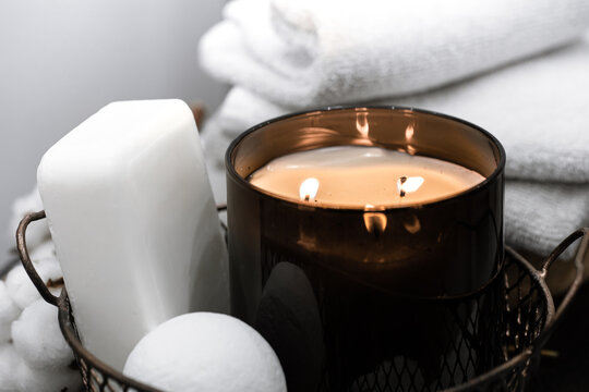 Cozy spa composition with body care products and candle close up.