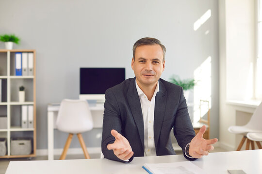 Portrait of happy businessman sitting at desk in office, looking at camera and talking