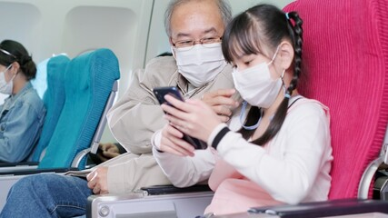 Asian grandfather is teaching to wear correctly the facial mask to his granddaughter.Coronavirus prevention on the airplane.travel concept