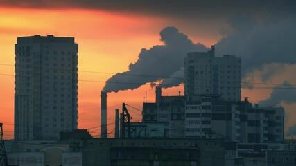 Fotobehang - Smokestacks emitting smoke in orange sunset sky over dark city skyline silhouette. Timelapse, 4K UHD.