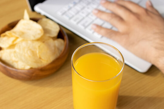 休憩時間におやつを食べ、ノートパソコンを使う男の手