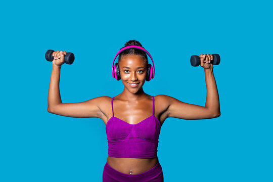 Fit young black woman weight lifting on blue background listening music