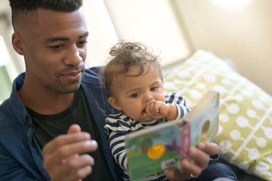 young african-american man reading book story to baby girl